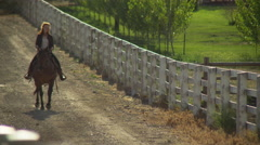 Young woman riding large horse through a farm Stock Footage
