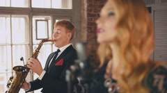 Jazz vocalist perform on stage with saxophonist in dinner jacket. Duet. Music Stock Footage