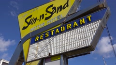 An old 1950s road sign advertises the Sun N Sand motor hotel and restaurant. Stock Footage