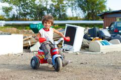 Cute little Roma boy sitting on small bike in front of street garbage dump. Stock Photos