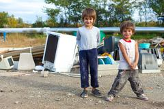 Cute little Roma boys standing in front of street garbage dump. Stock Photos