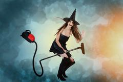 Young woman dressed as a witch riding a vacuum cleaner. Cleaning concept. Stock Photos