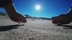 Sand Sifting Through Hands With Desert Sun Behind Stock Footage