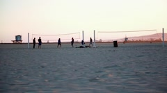 Cool shot of people by volleyball nets at beach in California during sunset Stock Footage