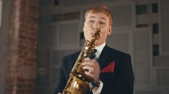 Saxophonist in dinner jacket play on golden saxophone. Jazz artist. Microphone Stock Footage