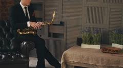 Saxophonist in dinner jacket sitting on chair with golden saxophone. Jazz artist Stock Footage