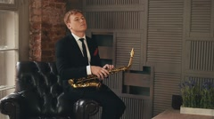 Saxophonist in dinner jacket stand on stage with golden saxophone. Jazz artist Stock Footage