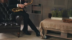 Saxophonist in dinner jacket sit on chair with golden saxophone. Jazz musician Stock Footage
