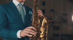 Saxophonist in blue suit playing on golden saxophone at stage. Elegance. Jazz Stock Footage