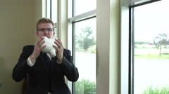 Businessman holding piggybank and crying Stock Footage