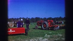 1961: couple inspect farming equipment at a yard sale at rural home IOWA Stock Footage