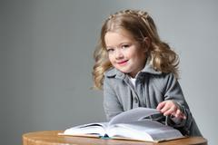 Portrait of baby girl in coat with a book. Close up. Gray background Stock Photos