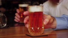 Close up on a glasses of lager resting on a bar in front of people Stock Footage