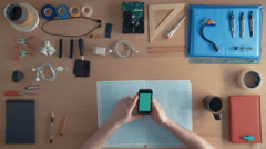 Top view software engineer is using cell phone smartphone on his desk full of Stock Footage