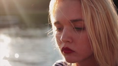 Beautiful young caucasian girl with blond hair and red lips on sunset in front Stock Footage