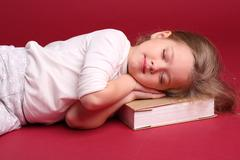 Baby sleeping on a book. Close up. Red background Stock Photos