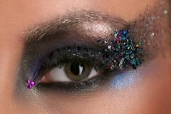 Woman's eye with makeup and colorful crystals. Close up Stock Photos