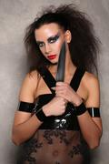 Dangerous woman with knifeand wild hair. Close up. Graybackground Stock Photos