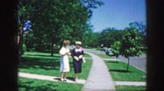 1961: two women walking animatedly in a beautiful street with lots of greenery Stock Footage