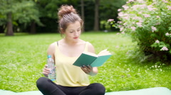 Girl drinking water while reading a book on exercising mat Stock Footage