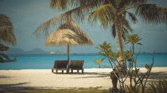 Two wooden lounge chairs under palm tent on beach Stock Footage