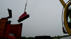 A small yellow crane lifts large pieces of red metal. Video about building Stock Footage