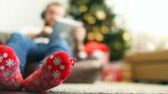 Man in bright Christmas socks using pad Stock Footage
