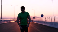 Runner man stretching and taking rest on road. Handsome Caucasian male fitnes Stock Footage