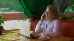Business woman wearing glasses working in cafe and talking on smart phone Stock Footage