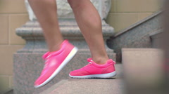Legs in sport shoes walking down stairs in slow motion Stock Footage