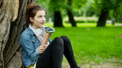 Happy girl sitting in the park and talking on loudspeaker Stock Footage