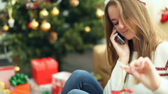 Pretty young girl in christmas cap talking on the phone Stock Footage