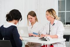 Two pretty young women nurses or doctors talking with female client in their Stock Photos