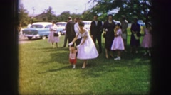 1961: lady in white dress helping a small child to walk at a family event Stock Footage