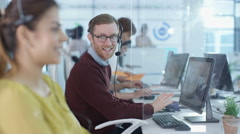 4K Portrait smiling customer service agent chatting with coworker in call center Stock Footage