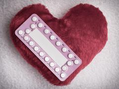 Oral contraceptive pills on red heart Stock Photos