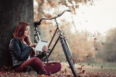 Girl under tree with bike. Stock Photos