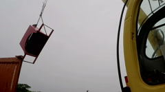 A small yellow crane lifts large pieces of metal. Stock Footage