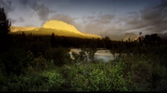 Stream flowing into lake at sunrise, Glacier National Park, MT Stock Footage