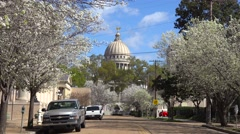 The capital dome of the statehouse in Jackson, Mississippi rises above a pretty Stock Footage