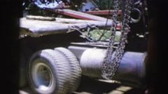 1961: a red truck carrying heavy chains is parked in a yard of a rural area IOWA Stock Footage
