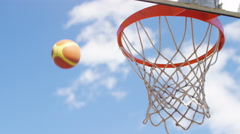 Close up of basketball scoring through the hoop, in slow motion Stock Footage