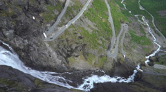 Serpentine road and waterfall between the mountains - Trollstigen, Norway Stock Footage