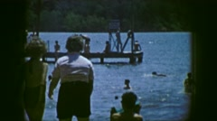 1961: the scene shows people swimming in a beach and a lifeguard overlooks Stock Footage
