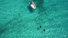 4K aerial of scuba divers in clear blue sea swimming with boat at Klein Curacao Stock Footage