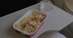 In plane on table is disposable tableware with a dish of rice and chicken and a Stock Footage