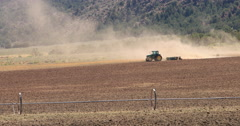 Hot desert mountain valley tractor dusty farm DCI 4K Stock Footage