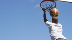 Basketball player does a reverse slam dunk, in slow motion Stock Footage