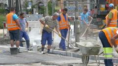 4K TL Construction Roadwork Hot porous Asphalt is applied loading in wheelbarrow Stock Footage