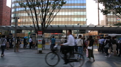 People waiting for bus and getting on bus at bus stop around Hakata train ST Stock Footage